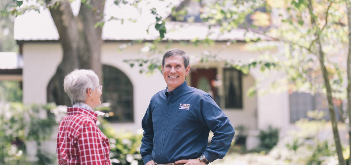 Dale Tadlock, President of Tadlock Roofing, poses with a homeowner