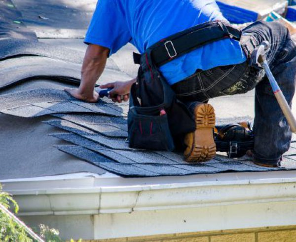 Roofer nailing down shingles